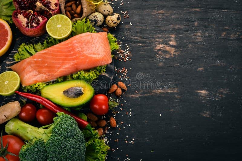 Alimento sano Peschi il salmone, l'avocado, i broccoli, gli ortaggi freschi, matto e frutti Su un fondo nero immagini stock
