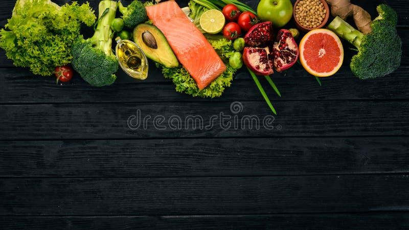 Alimento sano Peschi il salmone, l'avocado, i broccoli, gli ortaggi freschi, matto e frutti Su un fondo nero fotografia stock
