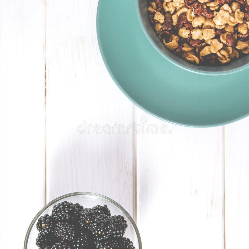 Alimento sano: una prima colazione sana dei fiocchi di granturco e delle bacche della mora su una tavola bianca dell'albero fotografia stock libera da diritti