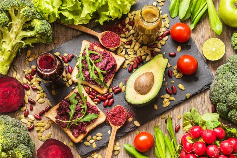 Alimento saudável do vegetariano Sanduíches e legumes frescos no fundo de madeira Dieta da desintoxicação Sucos frescos coloridos fotografia de stock