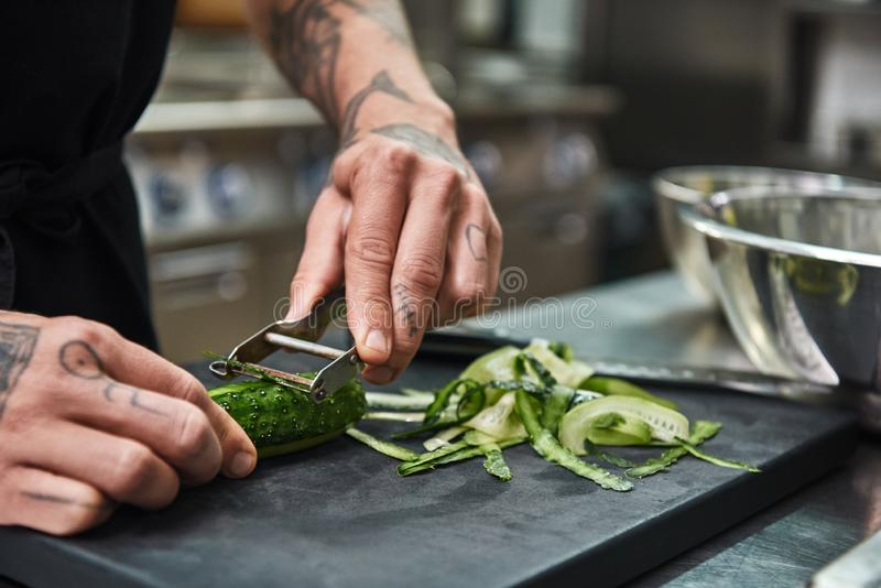 Alimento saudável Feche acima das mãos masculinas com as tatuagens bonitas que descascam o pepino para a salada ao estar em um re imagem de stock