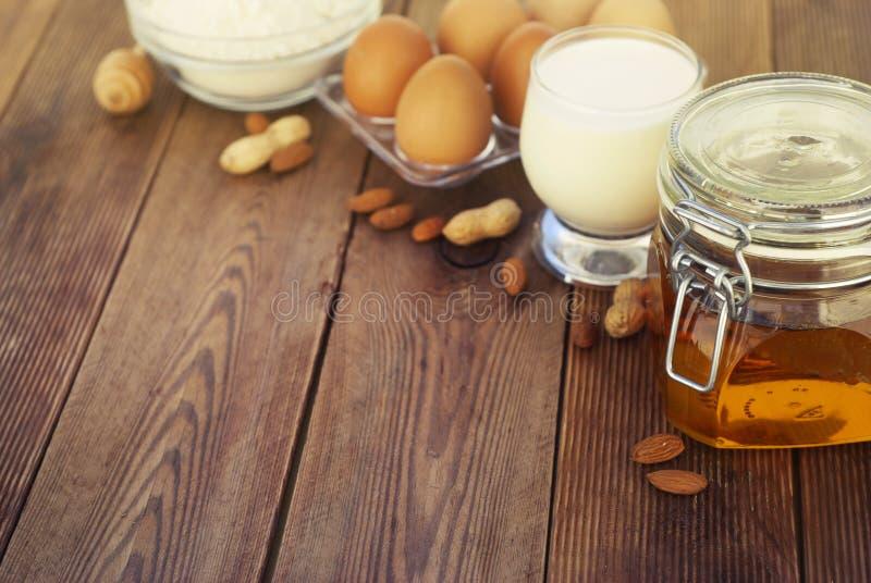 Alimento saudável Leite da amêndoa com mel, ovos frescos no fundo de madeira Tabela de madeira Copie o espaço imagem de stock royalty free