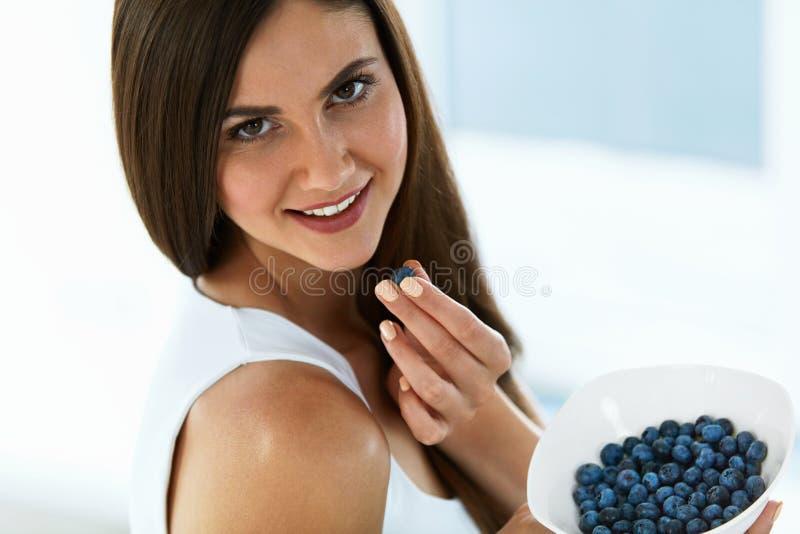 Alimento saudável Mulher feliz na dieta que come mirtilos orgânicos fotos de stock royalty free