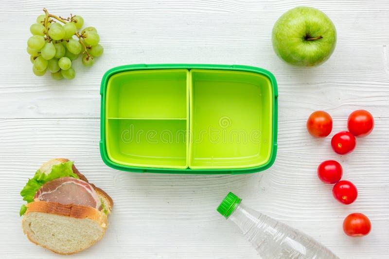 Alimento saudável na cesta de comida para o jantar do fundo branco da tabela da escola na opinião superior foto de stock