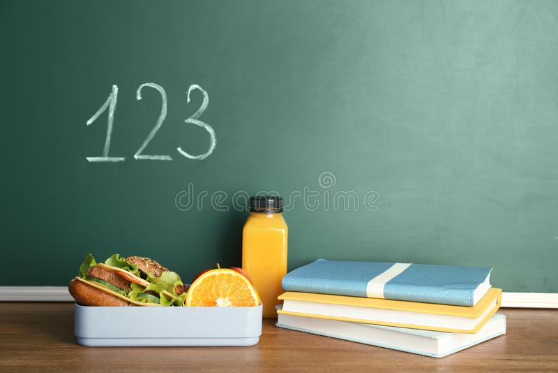 Alimento saudável para o aluno e os artigos de papelaria na tabela perto do quadro imagens de stock royalty free