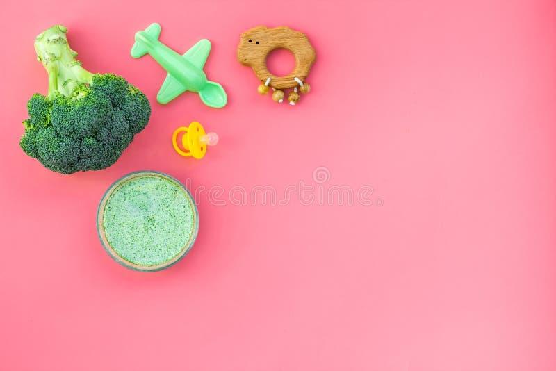 Alimento saudável para o bebê pequeno O puré vegetal com brócolis perto da chupeta e os brinquedos na opinião superior do fundo c imagem de stock