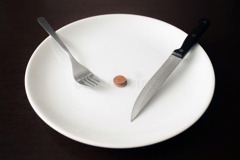 Alimento saudável, pobreza, dinheiro de salvamento: moedas em uma placa branca na sala de jantar imagem de stock