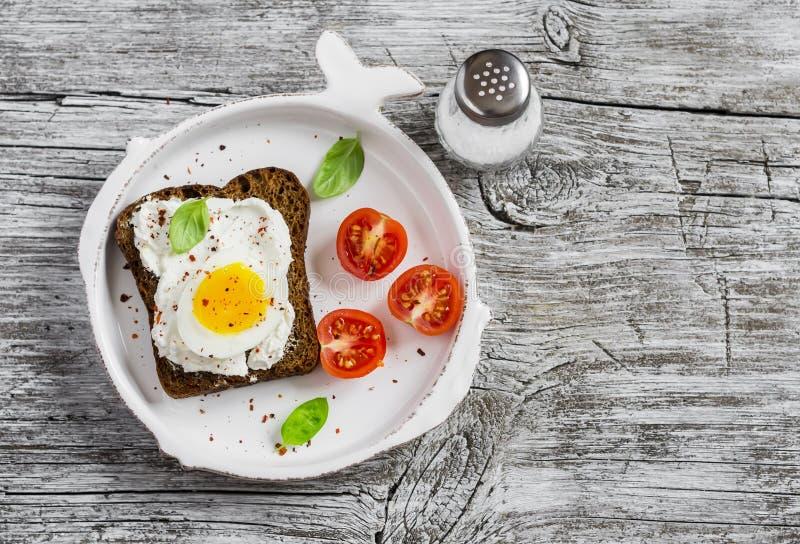 Alimento saudável - um sanduíche com pão de centeio, queijo macio e ovo cozido Em superfícies rústicas claras de uma madeira imagem de stock