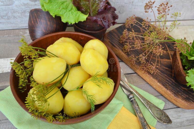Alimento saudável verde ou conceito comer da dieta Batatas fervidas com as ervas frescas na bacia rústica e na tabela velha foto de stock