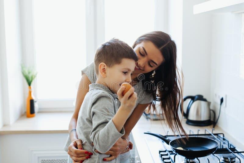 Alimento saud?vel em casa Fam?lia feliz na cozinha A filha da mãe e da criança está preparando ovos fotos de stock royalty free