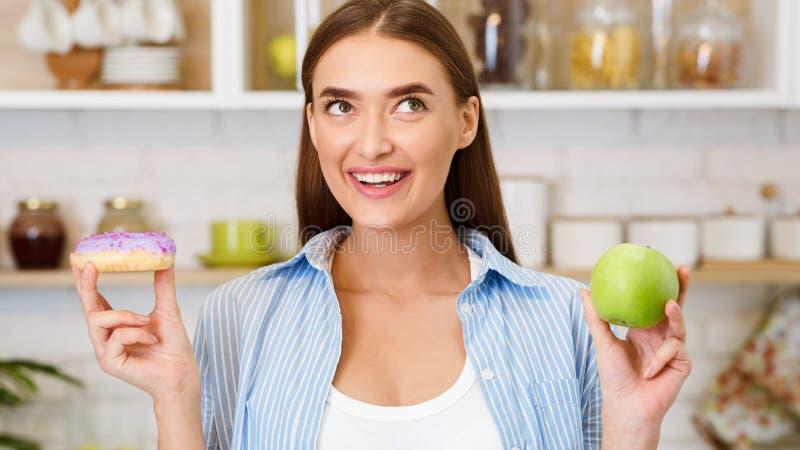 Alimento saud?vel Mulher que escolhe entre frutos e doces fotografia de stock