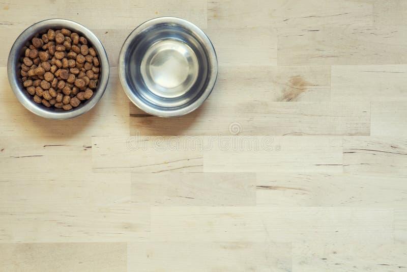 Alimento seco para gatos Duas bacias Superfície de madeira foto de stock