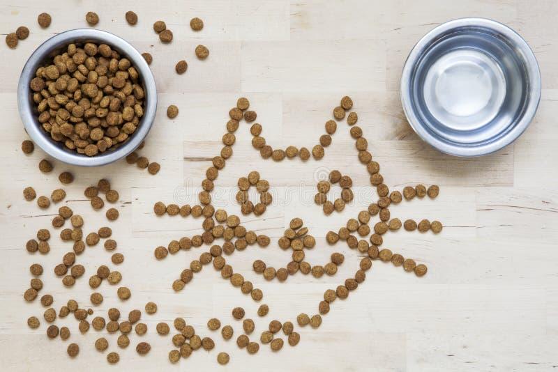 Alimento seco para los gatos Dos tazones de fuente Superficie de madera Forma del gato imágenes de archivo libres de regalías