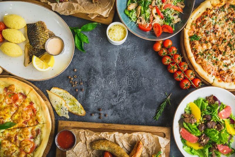 Alimento sortido ajustado com espaço da cópia Reforços de carne de porco, pizza, salada, peixes e salsichas grelhados com batatas foto de stock
