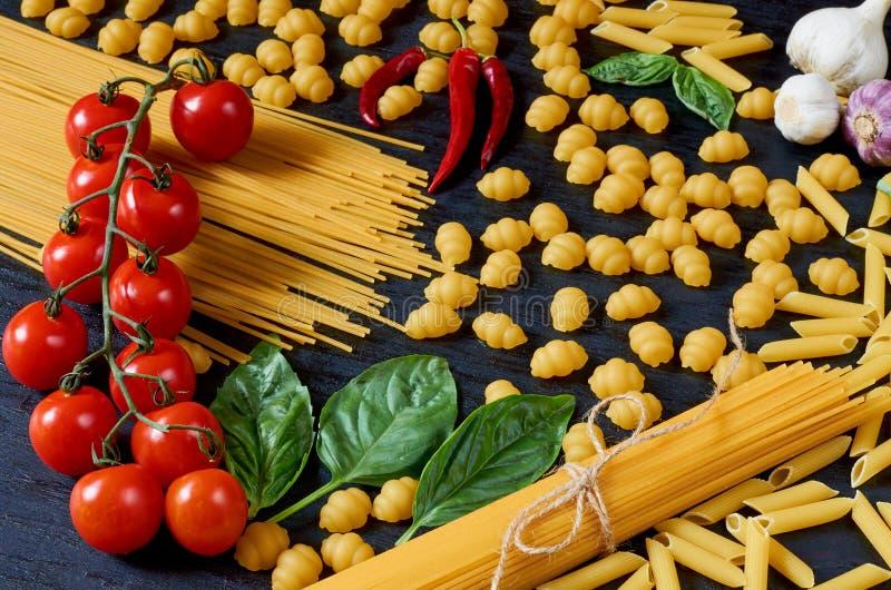 Alimento, spezie ed ingredienti tradizionali italiani per la cottura come il basilico, i pomodori ciliegia, il peperoncino, l'agl fotografia stock libera da diritti