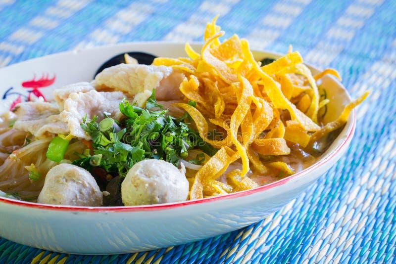 Alimento tailandês - fritada #6 do Stir sopa de macarronete com bola e carne de porco de peixes na esteira azul fotografia de stock