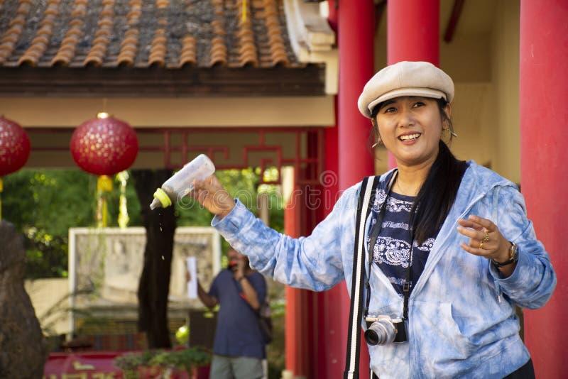 Alimento tailand?s da visita e da alimenta??o da mulher para gostar da carpa na lagoa do jardim chin?s no centro cultural Tailand fotos de stock royalty free