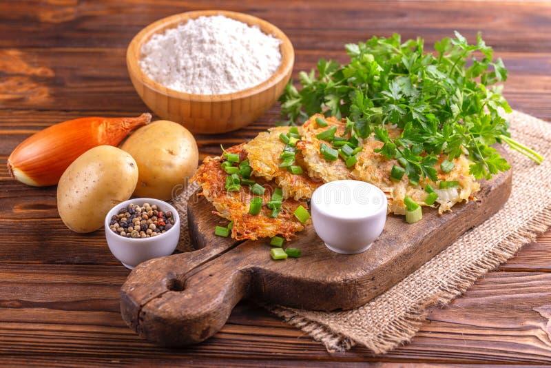 Alimento tradizionale casalingo di celebrazione di Chanukah dei pancake di patata con gli ingredienti sul tagliere d'annata immagini stock libere da diritti