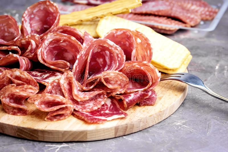 Alimento Tray With Delicious Salami Pieces da placa cortada do presunto e da carne dos biscoitos e das varas de pão fotografia de stock royalty free