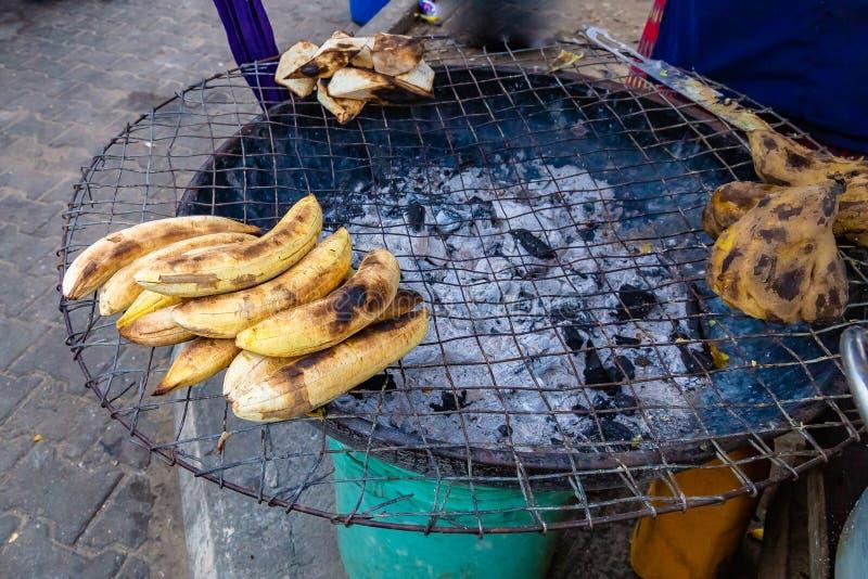 Alimentos da rua em Lagos Nigéria; grade do carvão vegetal da borda da estrada com 'batata doce' roasted, banana-da-terra e a bat imagens de stock