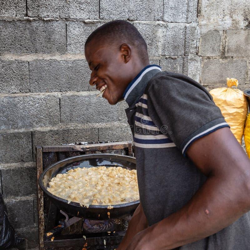 Alimentos da rua em Lagos Nigéria; vendedor feliz que frita akara ao longo da rua fotografia de stock