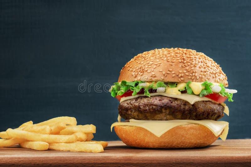 Alimentos de preparación rápida Cheeseburger y patatas fritas en un tablero de madera, en fondo oscuro fotos de archivo