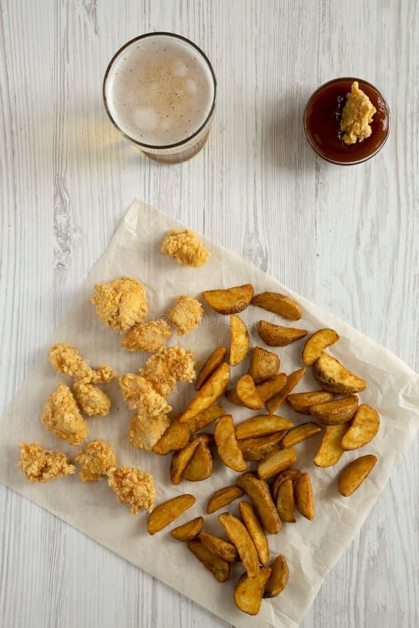 Alimentos de preparación rápida: cuñas de la patata, mordeduras del pollo, cerveza y salsa fritas en una tabla de madera blanca,  foto de archivo