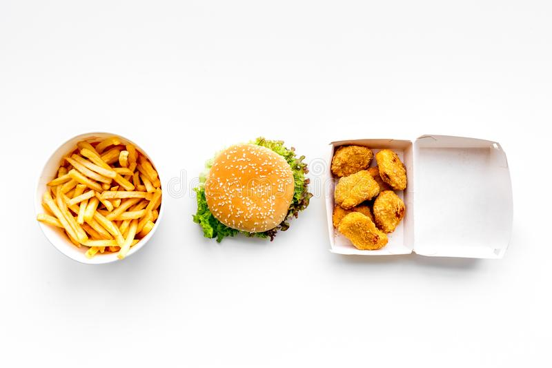 Alimentos de preparación rápida Pepitas, hamburguesas y patatas fritas de Chiken en la opinión superior del fondo blanco imagenes de archivo