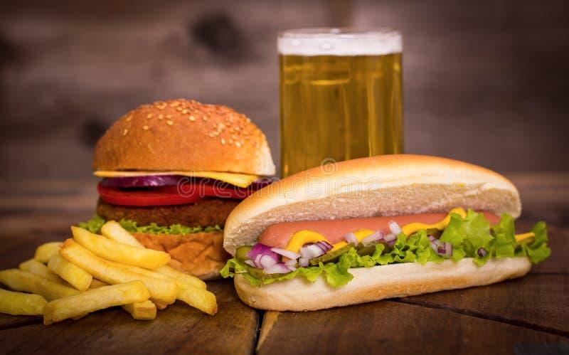Alimentos de preparación rápida - perritos calientes, hamburguesa y patatas fritas imágenes de archivo libres de regalías