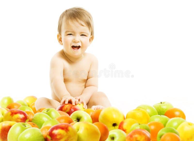 Alimentos para niños Niño que se sienta dentro de las frutas sobre el fondo blanco Él fotos de archivo libres de regalías