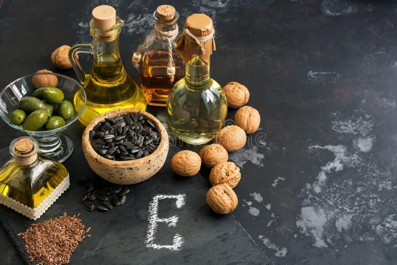 Alimentos ricos na vitamina E em um fundo rústico escuro Óleo, porcas, sementes Alimento saudável para o rejuvenescimento Foco se imagens de stock royalty free