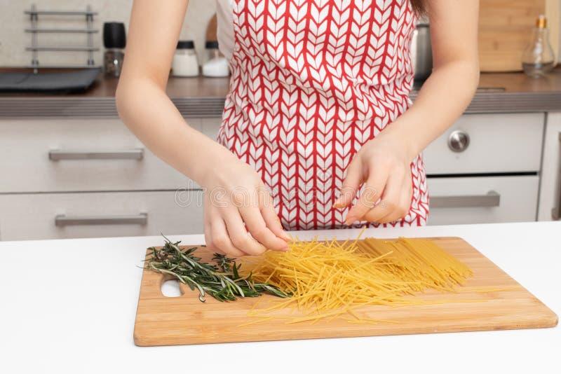 Alimentos saudáveis e saudáveis Mãos femininas quebram espaguete em pedaços foto de stock