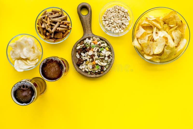 Aliments de préparation rapide pour l'observation de TV Casse-croûte sur le bureau Puces, écrous, biscottes et bière sur l'espace image libre de droits