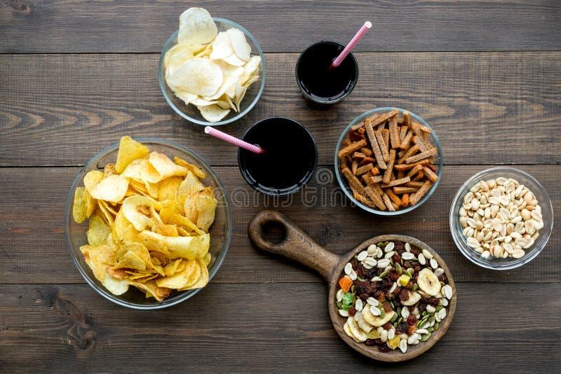 Aliments de préparation rapide pour l'observation de TV Casse-croûte sur le bureau Puces, écrous, biscottes et soude sur la vue s photographie stock libre de droits