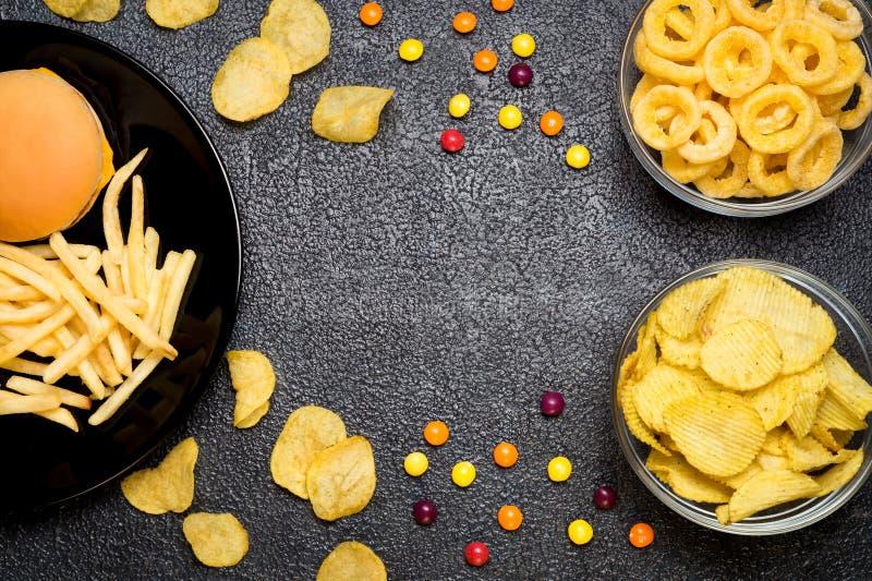 Aliments de préparation rapide : vue supérieure d'hamburger, de pommes frites, de pommes chips, d'anneaux et de Ca photo stock