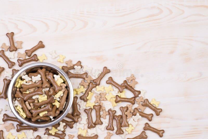 Aliments pour chiens dans une cuvette sur un fond en bois photos stock