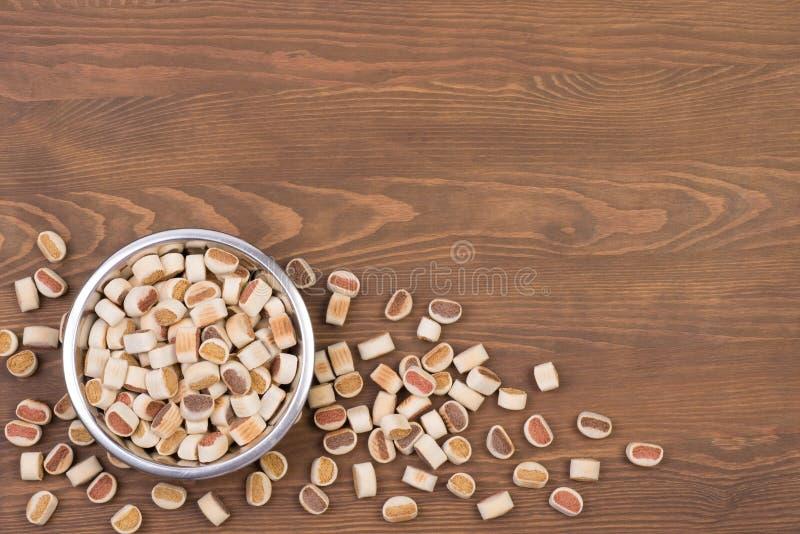 Aliments pour chiens dans une cuvette sur un fond en bois images libres de droits