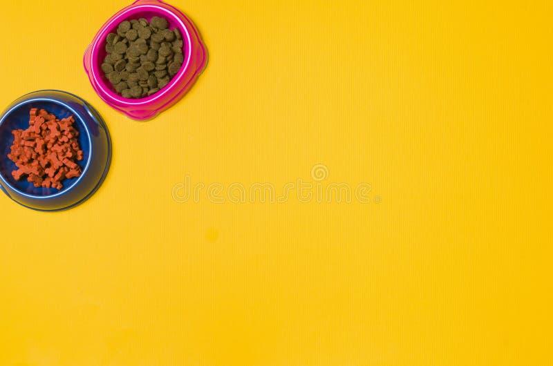 Aliments pour chiens et accessoires sur la vue supérieure de fond jaune photographie stock