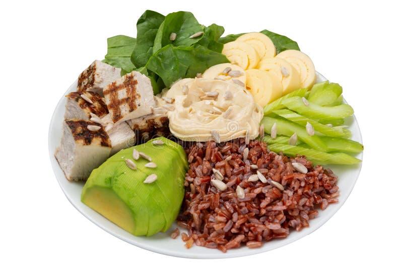 Aliments sains dans une cuvette, une viande et un houmous grillé, un riz et une omelette brune, un céleri et un avocat, cuvette d photo stock