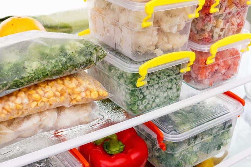 Aliments surgelés dans le réfrigérateur Légumes sur les étagères de congélateur images libres de droits
