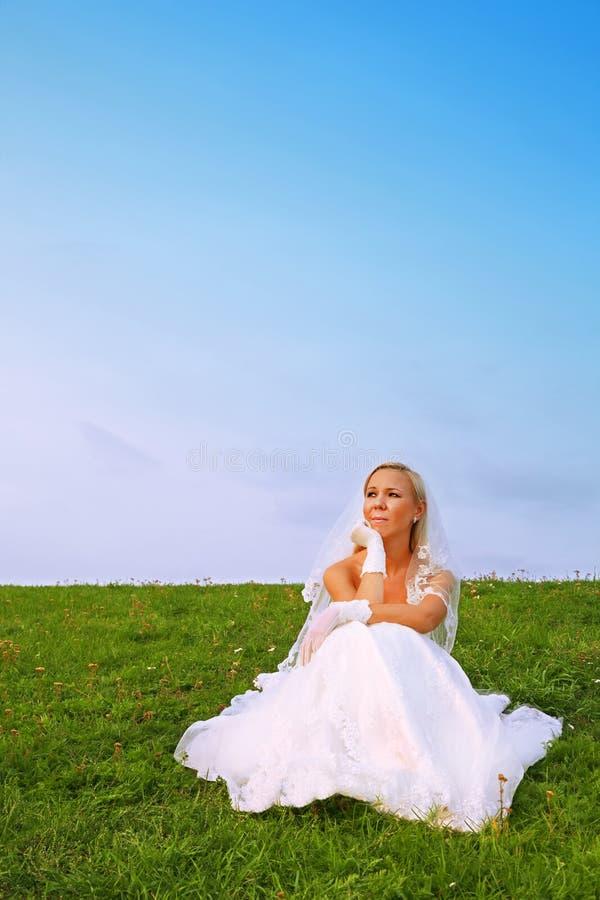 Alineada blanca que desgasta de la novia que se sienta en hierba fotos de archivo libres de regalías