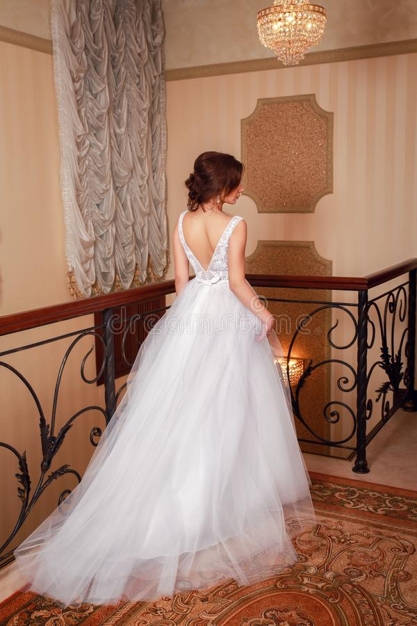Alineada de boda hermosa Novia en vestido de boda en un apartamento de lujo Parte posterior de la visión imagen de archivo