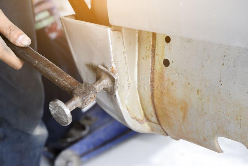 Alinee el coche del cuerpo del metal con el martillo en la industria del automóvil - b auto fotografía de archivo
