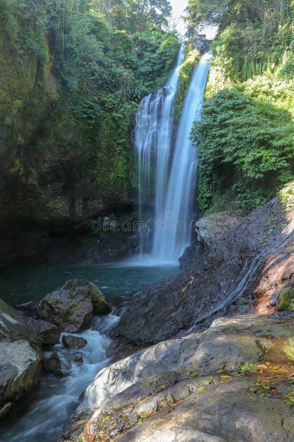 Aling Aling vattenfall i Sambangan bergområde på den Bali ön Vagga massiven och kanjonen som täckas med tropiska växter arkivfoto