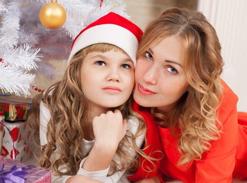 Alisa&Alexandra Menina do Natal e tampão e árvore vermelhos da mãe a imagens de stock