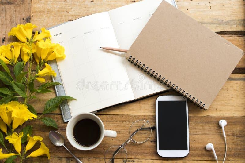 Alisadora del cuaderno, teléfono móvil para el trabajo del negocio con café caliente fotografía de archivo