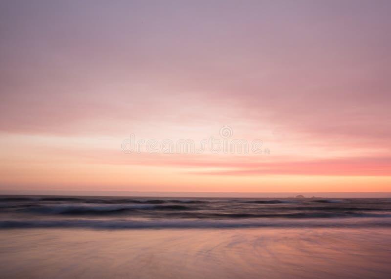 Alise los colores en colores pastel de la puesta del sol sobre el océano fotos de archivo