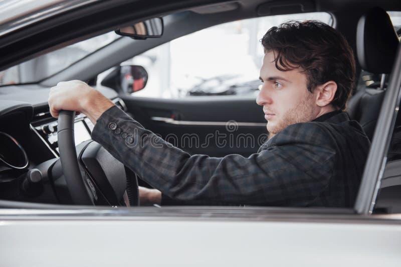 Aliste para la prueba de conducción Retrato de un hombre de negocios hermoso que conduce el coche fotografía de archivo