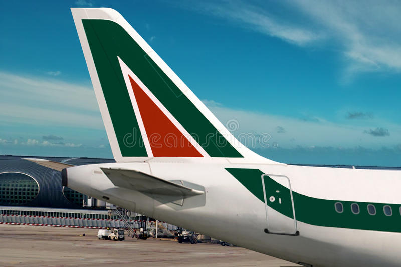 Alitalia airplane. Airplane with the symbol of Alitalia airline company on the tail. Sky area is free for your text stock image