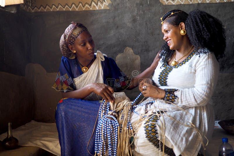 Alitena Etiopien - 2 Juni 2019: Två kvinnor arbetar på att pryda med pärlor en traditionell etiopisk gifta sig garnering fotografering för bildbyråer